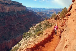 Woman hiking on a stone path with natural steps leading down the cliffs of Grand Canyon National Park. Hiking down to the Vally on red and rocky pathways. Trekking in between red mountains and rocks.