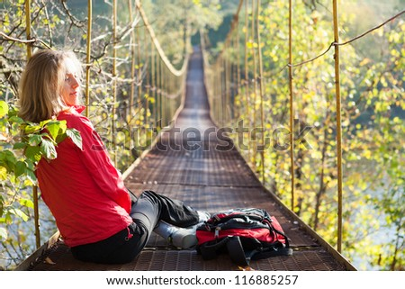 Woman hiking sitting in suspension bridge and resting on a sunny bright day
