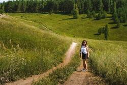 Woman hiking through the high meadows near the green fields