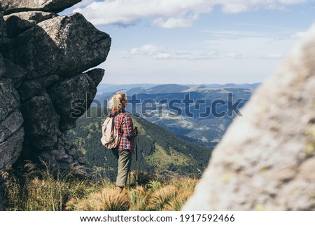 Woman hiking with backpack and trekking poles on summer day. Nature tourism in Ukrainian Carpathian mountains. Photo stock ©