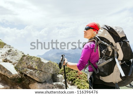 Woman hiking with backpack in mountains, climbing and trekking in Corsica France