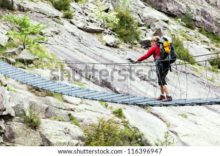 Woman hiking with backpack in mountains, crossing steel suspension bridge, trekking in Corsica France