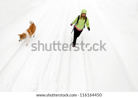 Woman hiking with dog on winter road and snow, walking and trekking in cold white nature