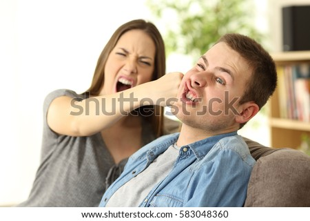 Woman hitting her boyfriend sitting on a couch in the living room in a house interior