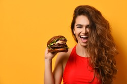 Woman hold big barbecue burger sandwich with hungry mouth happy screaming laughing on yellow background. Fast food concept.