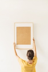 Woman hold blank photo frame with empty copy space on white background. Minimal artist work concept.