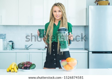 Woman hold blender with green smoothie. Healthy eating lifestyle. Blonde healthy girl drinks green smoothie. Vegan vegetarian vegetable concept. Blending cocktail in the blender machine #1526874581
