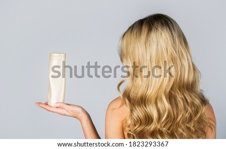 Woman hold bottle shampoo and conditioner. Woman holding shampoo bottle. Beautiful blonde girl with a bottle of shampoos in hands. Girl with shiny and long hair. Woman long hair.