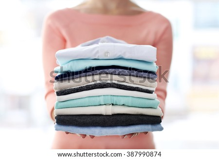 Woman hold clothes pile, close up #387990874