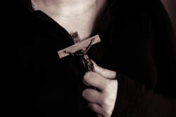 Woman hold crucifix to chest. Wooden crucifix in a female hand