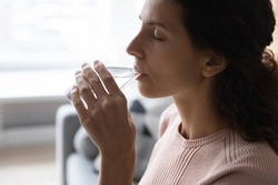 Woman hold glass makes sip of still water, close up side view face. Young female looking sick feels unwell reduces thirst drinks fresh aqua, keep diet, weight loss, healthcare, natural balance concept