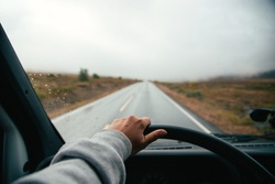Woman hold steering wheel, drive old vintage camper van on empty highway or high altitude mountain road during adventure road trip. Vanlife lifestyle concept