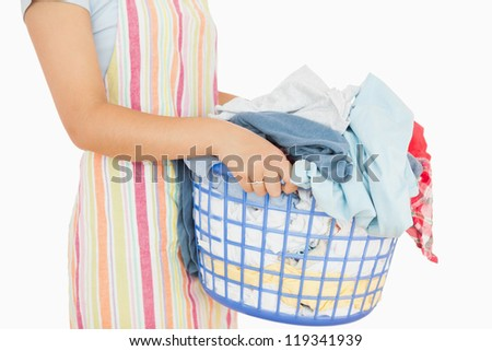 Woman holding a basket full of laundry in a white background
