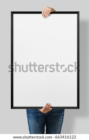 Woman holding a blank poster with black frame mockup isolated on a gray background.  #663416122