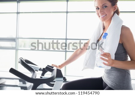 Woman holding a bottle of water and riding an exercise bike