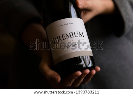 Woman holding a bottle of wine with a label mockup