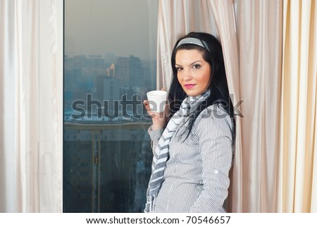 Woman holding a cup of coffee and sitting in front of window with city view in her home