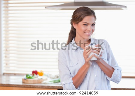 Woman holding a cup of coffee in her kitchen