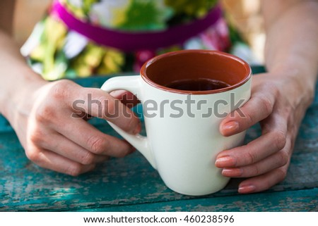 Woman holding a cup of tea above the wooden table. #460238596