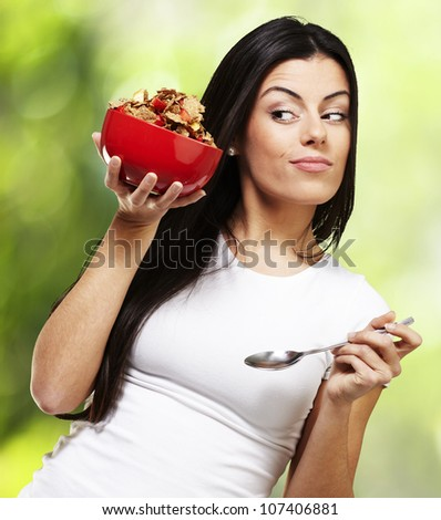 woman holding a delicious red breakfast bowl against a nature background