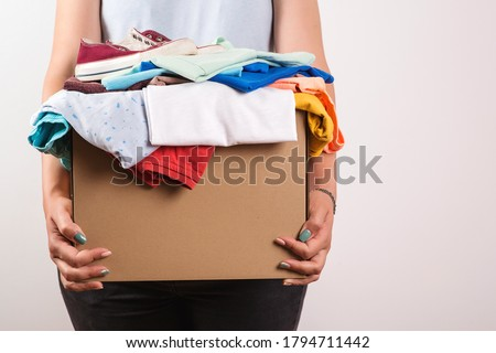 Woman holding a donate box. Donation box for giving. Sharity social activity. Cardboard box with clothes for charity. Female volunteer holding donations. Case full of clothing for giving. Help poor. Foto stock ©