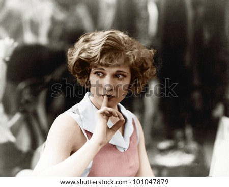 Woman holding a finger in front of her mouth signaling to be quiet