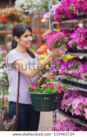 Woman holding a flower and a basket in garden centre