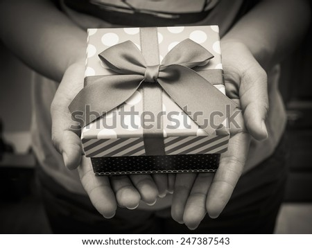 Woman holding a gift box in a gesture of giving with black and white effect