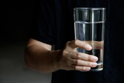 Woman holding a glass of water on a dark background.