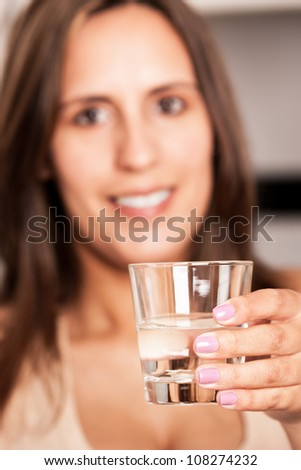 Woman holding a glass of water, she is out-of-focus