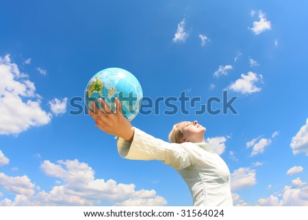 woman holding a globe under blue sky