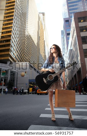 Woman holding a guitar and some shopping bags in the middle of a city street