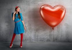 Woman holding a heart shaped balloon