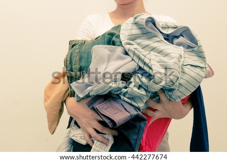 Woman holding a huge pile of clothes . Laundry, Clothing