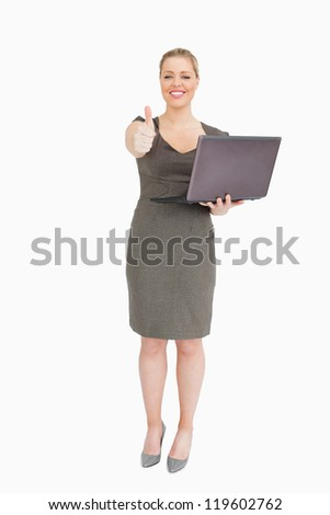 Woman holding a laptop while she is thump up against white background