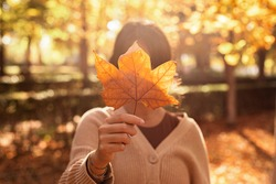Woman holding a leaf covering her face on a sunny autumnal afternoon strolling in the park