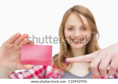 Woman holding a loyalty card while showing it with a finger against a white background