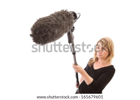 Woman holding a microphone boom against a white background. Selective focus on the furry microphone windshield.