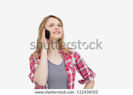 Woman holding a mobile phone while looking up against a white background