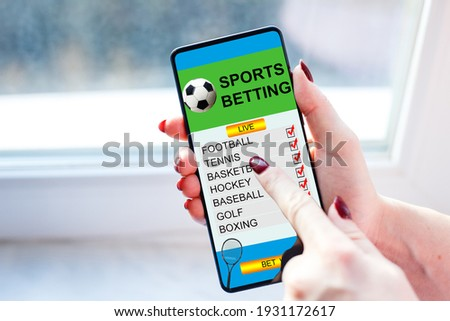 woman holding a mobile phone with sports betting website in the screen. Stok fotoğraf ©