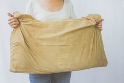 Woman holding a pillow with dirty stains, yellow stains, sweat stains. Cleaning concept.