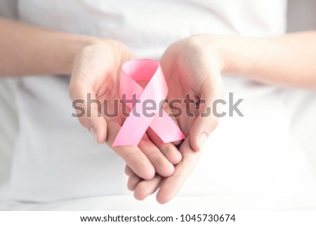 Woman holding a pink ribbon in her hands. Breast cancer awareness concept #1045730674