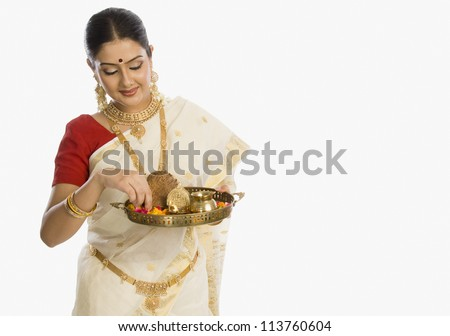 Woman holding a plate of religious offerings