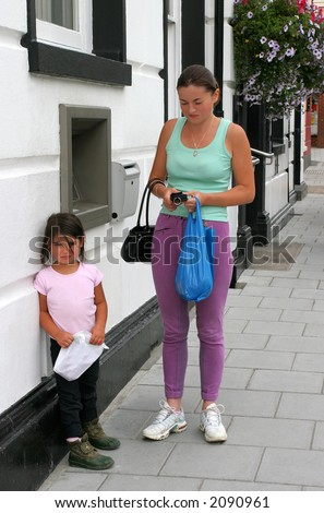 Woman holding a purse with a little girl standing next to her outside a bank cash point with a miserable look on their faces.