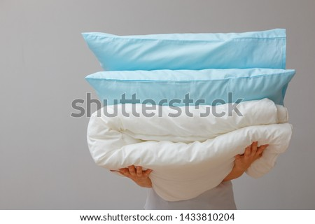 Woman holding a quilt and pillows on a background of gray wall. Stack bedding for sleep. Household.