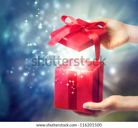 Woman holding a red gift box on a blue holiday lights background