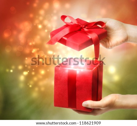 Woman holding a red gift box on a bright holiday lights background