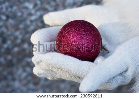 Woman holding a red shiny Christmas tree bauble wearing red gloves