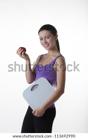 woman holding a set of bathroom weight scales about to eat a apple wanting to keep fit and healthy