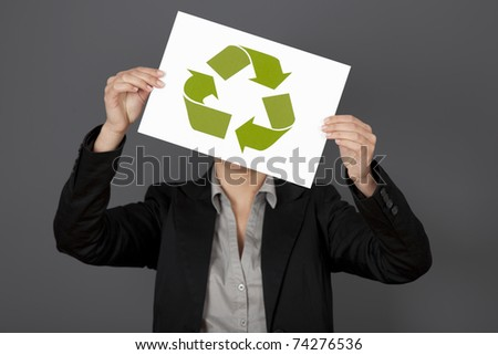 Woman holding a sheet of paper with the recycling symbol